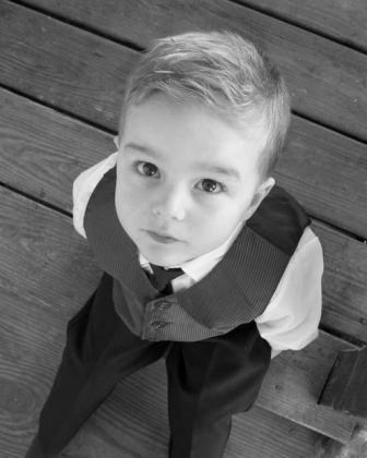 Little boy with asperger syndrome behavior in suit looking up at camera