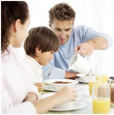 Parents giving child breakfast as part of an autism diet plan