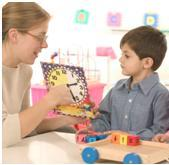 Teacher applying autism treatment techniques to child using clock
