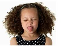 little girl sticking her tongue out and displaying symptoms of defiant children