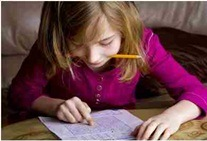 child with attention and memory problems looking at paper with pencil in hand displaying good study tips