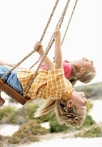 children swinging with their heads upside down displaying a symptom of a sensory processing disorder