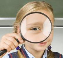 Child holding magnifying glass to eye with visual input dysfunction