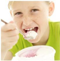 A child taking a bite of food with symptoms of oral defensiveness and dysfunction